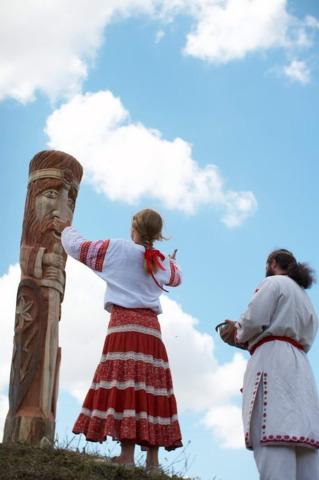 Adeptes de la foi ancestrale ukrainienne devant une représentation de Perun..